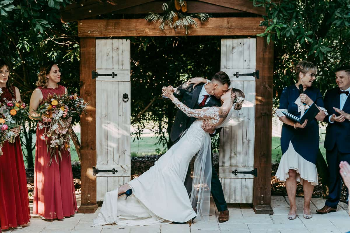 groom dipping bride and kissing at wedding alter